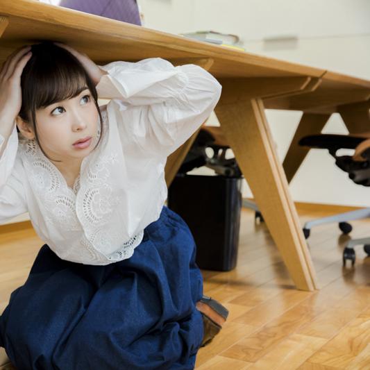 地震発生で机の下に避難する女性