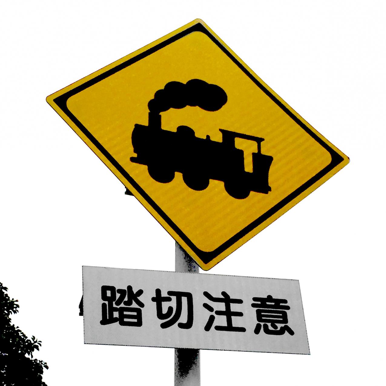「踏切注意」の道路標識。煙をあげる機関車のイラストで表現されている。